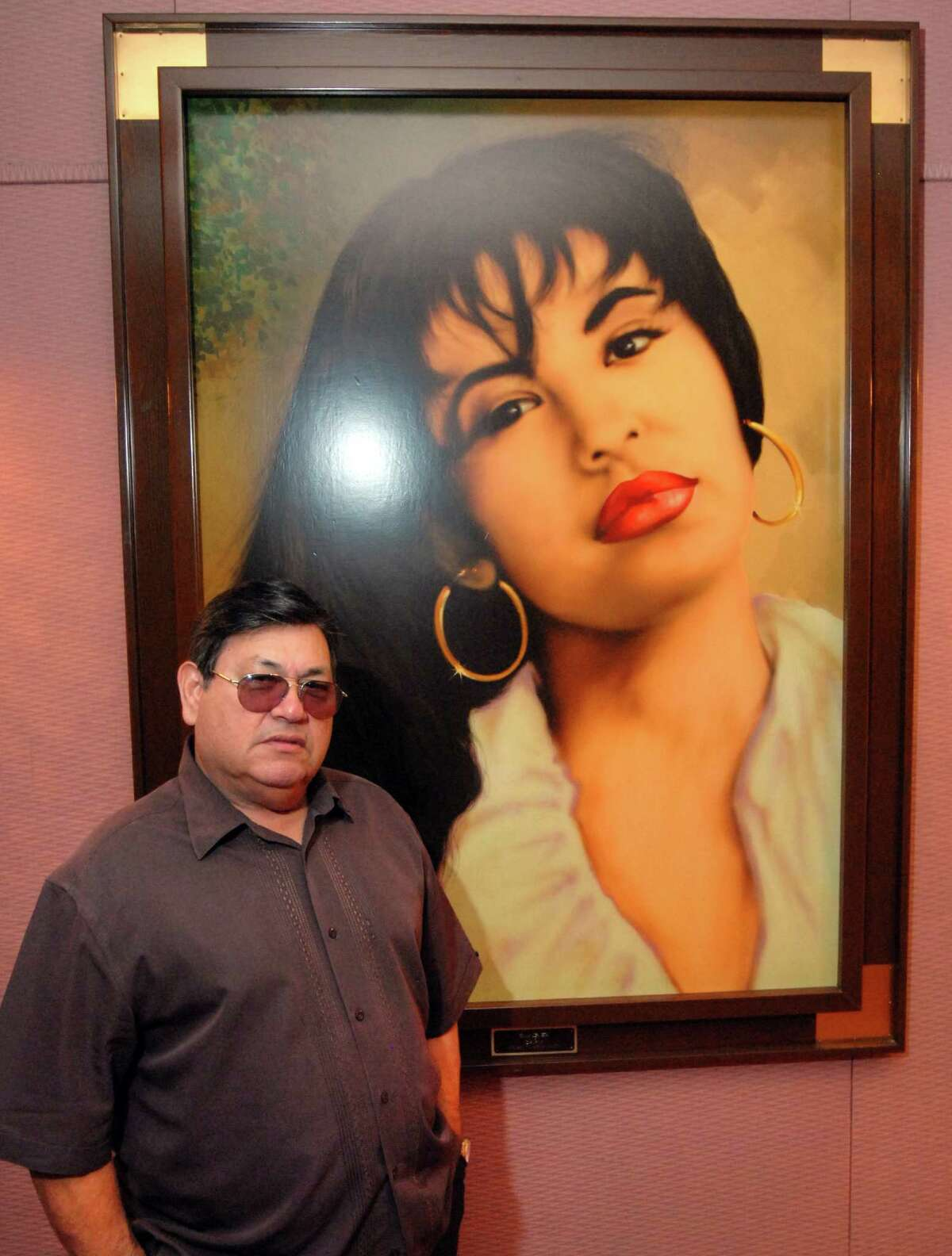 """FILE - In this June 24, 2011 file photo, Abraham Quintanilla, the father of the late singer Selena, poses in front of an airbrush portrait of her, a gift from a fan after the Tejano star's death, in a Q Productions' studio, in Corpus Christi, Texas, where Selena made her last recording. Selena?'s family is working with Acrovit, a tech company based in San Diego, in the creation of a digital clone of the beloved singer that would allow her fans to see her singing ?""""live"""" with Los Dinos. (AP Photo/Paul Iverson, File) ORG XMIT: XLAT121"""