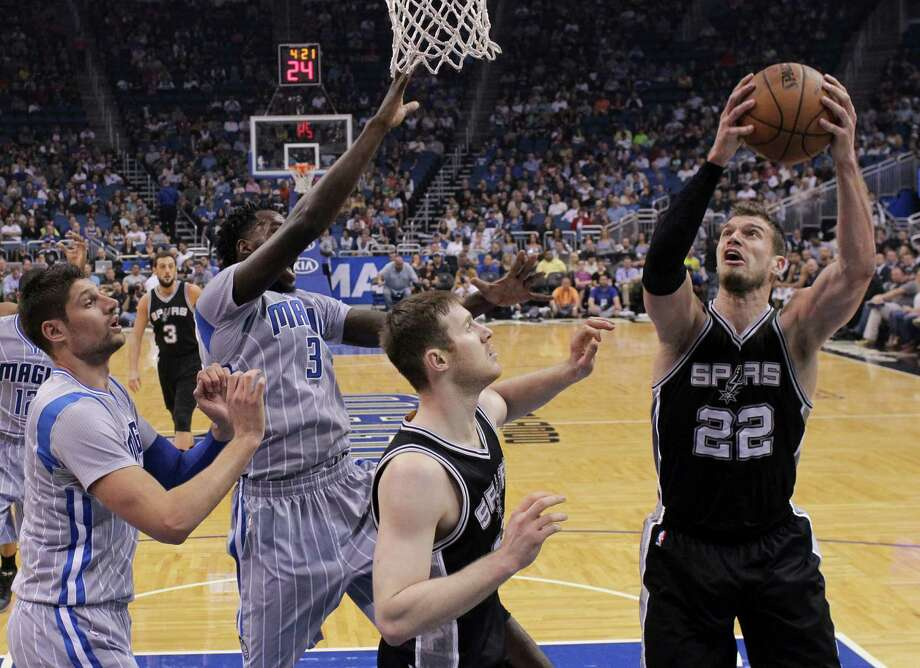 The Spurs' Tiago Splitter goes up for a shot against Orlando Magic's Nikola Vucevic (left) and Dewayne Dedmon (3) during the first half on April 1, 2015, in Orlando, Fla. Photo: John Raoux /Associated Press / AP