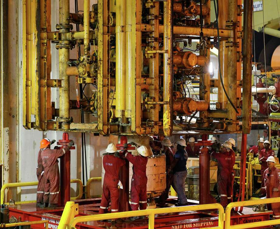 Workers secure the Deepwater Horizon's blowout preventer after lifting it from the Gulf of Mexico in September 2010. Investigations into the 2010 spill disaster found flaws in the devices' design. Photo: Pat Semansky, STF / ap