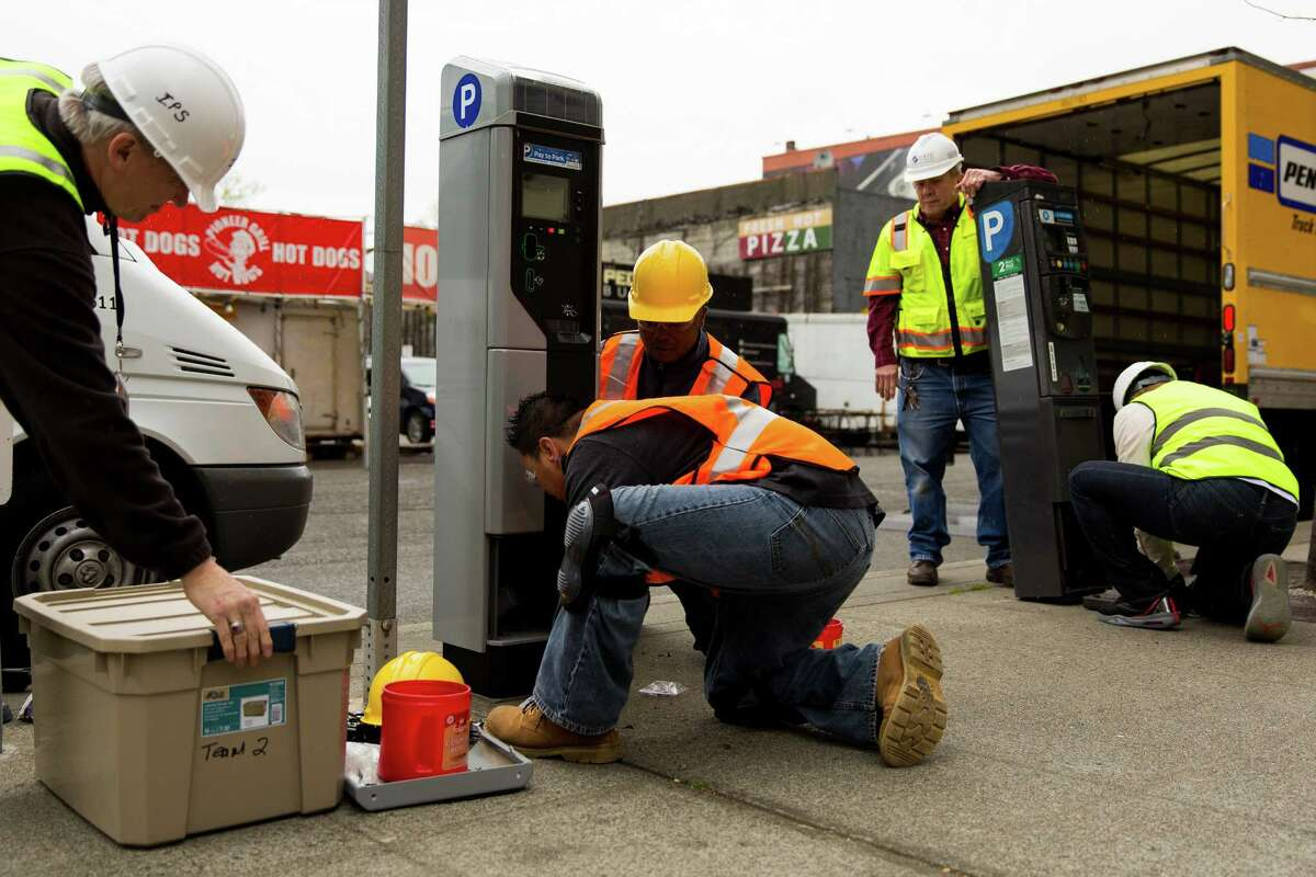SDOT employees work to swap an old parking station, right, out for one of 2,200 new smart parking pay stations, left, on Monday, April 13, 2015, near CenturyLink Field in Seattle, Washington. The City of Seattle selected the IPS Group to replace or retrofit all of the city?•s on-street parking pay stations by the end of 2016, boasting a higher level of customer service, communications reliability and variable