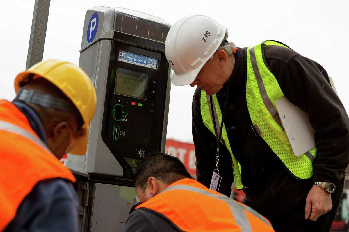 SDOT employees work to install one of 2,200 new smart parking pay stations Monday, April 13, 2015, near CenturyLink Field in Seattle, Washington. The City of Seattle selected the IPS Group to replace or retrofit all of the city?•s on-street parking pay stations by the end of 2016, boasting a higher level of customer service, communications reliability and variable