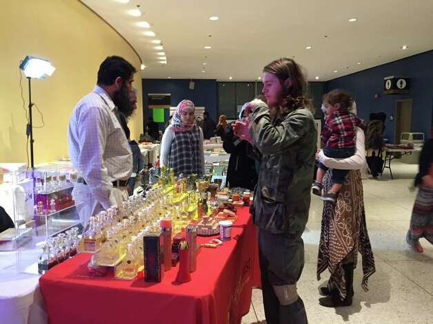 A potential customer tries attar (perfume) at a stall at Islamic Circle of North America convention presented on Saturday, April 11, at the Empire State Plaza Convention Center. (Azra Haqqie / Times Union)