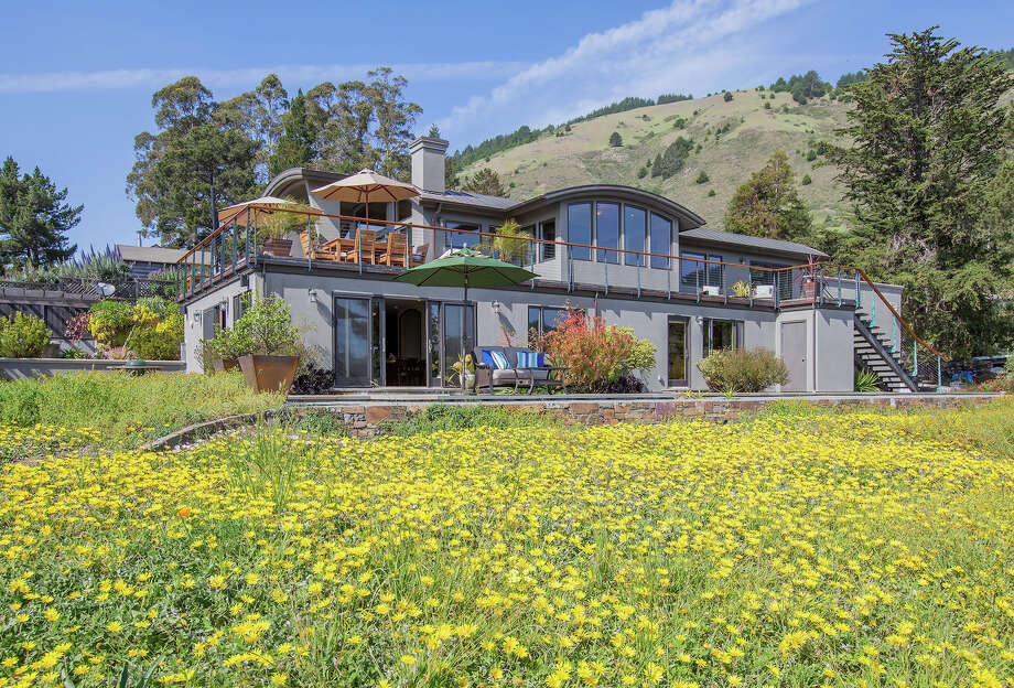 Wildflowers and tree-studded hills flank the Stinson Beach home built in 2007.