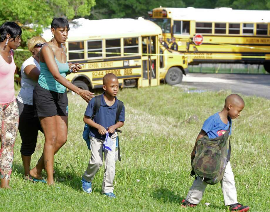 Ma'lique Brown, 7, right, and his brother, Ja'Kal Brown, 8, are led away by their grandmother Marilyn Williams after the HISD bus crash. Photo: Melissa Phillip, Staff / © 2015  Houston Chronicle