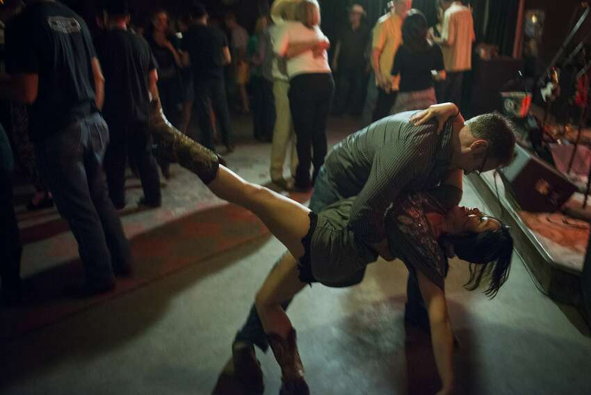 Patrons dance at The White Horse bar in Austin, Texas, U.S., on Friday, April 3, 2015. About 900,000 people live in the city of Austin and that number is expected to reach nearly 1.3 million by 2040, a 40 percent increase, according to city figures. More than 100 people move to the city a day, according to the city's demographer. Photographer: Matthew Busch/Bloomberg