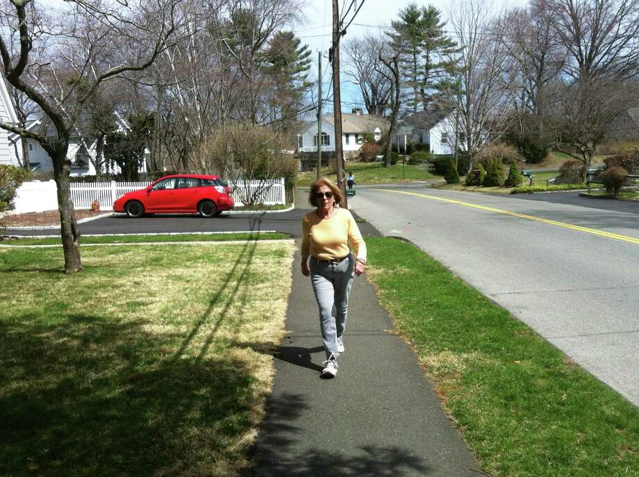 Elaine Kilbourn, a town of Darien employee walks along Park Place, on a loop she walks every weekday during her lunch hour.  Kilbourn is the Darien Health Department's poster child for a new social media campaign promoting regular exercise for residents. Photo: Martin Cassidy / Darien News