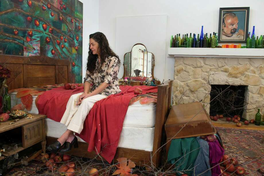 "Artist Elizabeth Rodriguez poses for a portrait in an installation of her first one-person exhibit at Bihl Haus Arts titled ""On the Eve of Consciousness."" The bedroom installation is inspired by a friend of Rodriguez who suffers from alcoholism and drug addiction. Photo: Matthew Busch /For The Express-News / © Matthew Busch"