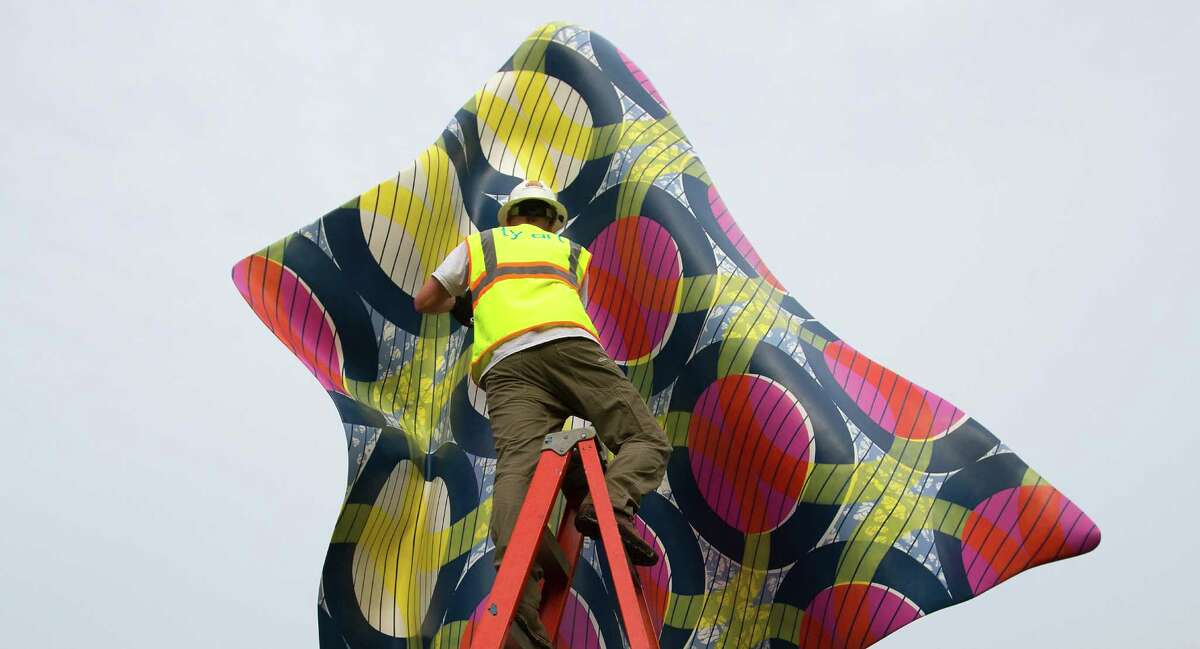 Crew members with TYart prepare to install Wind Sculpture IV by London-based artist Yinka Shonibare, at Hermann Park, Tuesday, April 14, 2015, in Houston. The sculpture, which is nearly 20 feet high and 11 feet wide at its widest point, captures the movement of a billowing bolt of fabric, the ripple seemingly paused in time. Wind Sculpture IV is one work in Shonibare's series inspired by ship sails. (Cody Duty / Houston Chronicle)