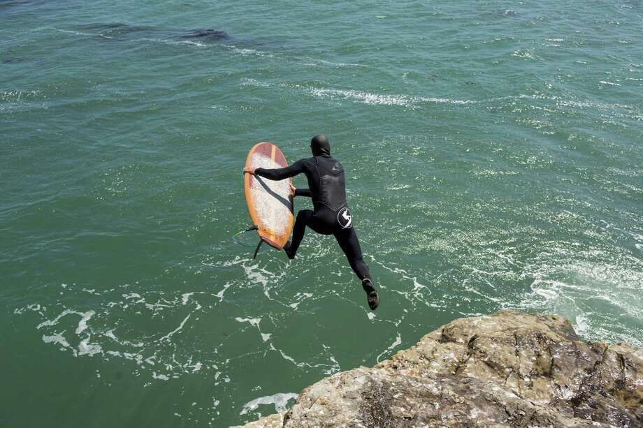 Tyler Fox, a Titans of Mavericks big-wave surfer, plunges into the water with his wooden Ventana surfboard at Steamer Lane in Santa Cruz. Photo: Jason Henry / Special To The Chronicle / ONLINE_YES