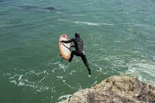 Tyler Fox, a Titans of Mavericks big-wave surfer, plunges into the water with his wooden Ventana surfboard at Steamer Lane in Santa Cruz.
