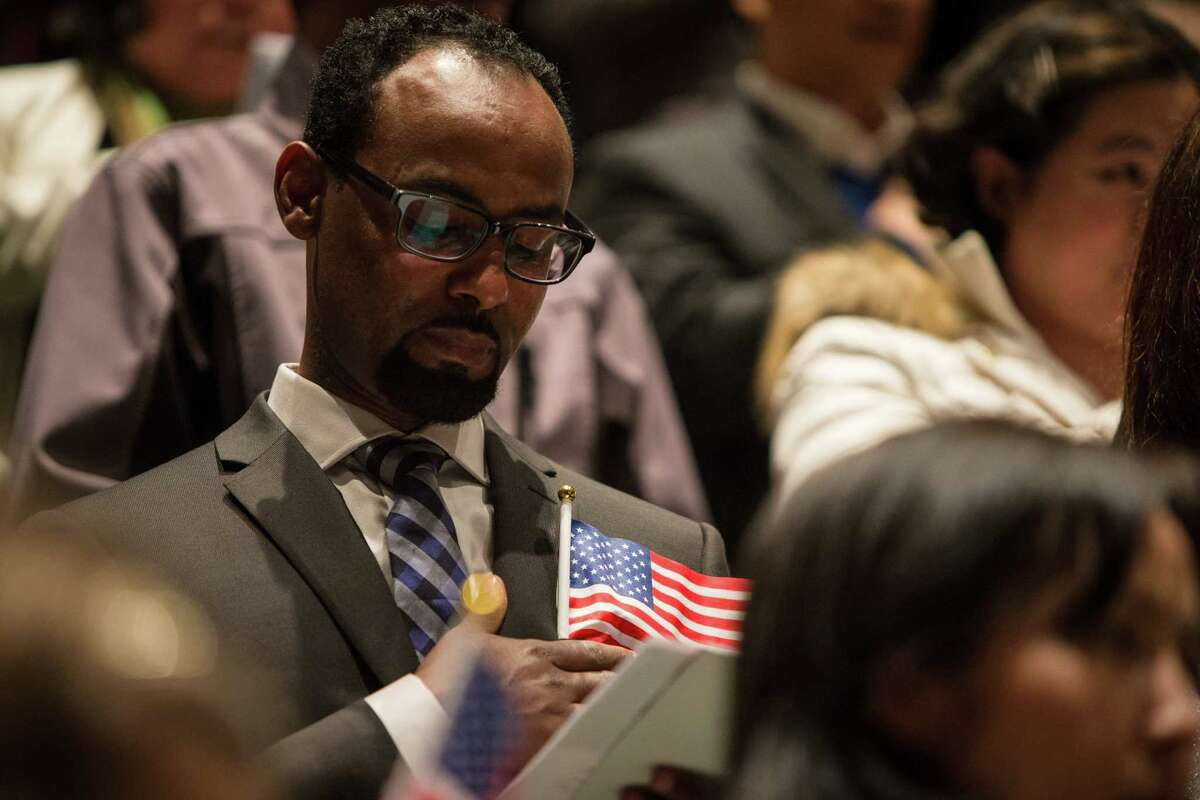 A candidate holds an American flag while saying the Pledge of Allegiance at the National Library Week annual naturalization ceremony in the Seattle Public Library on Monday, April 13, 2014. Seattle District Director Anne Arries Corsano welcomed 75 new citizens with the Oath of Allegiance.