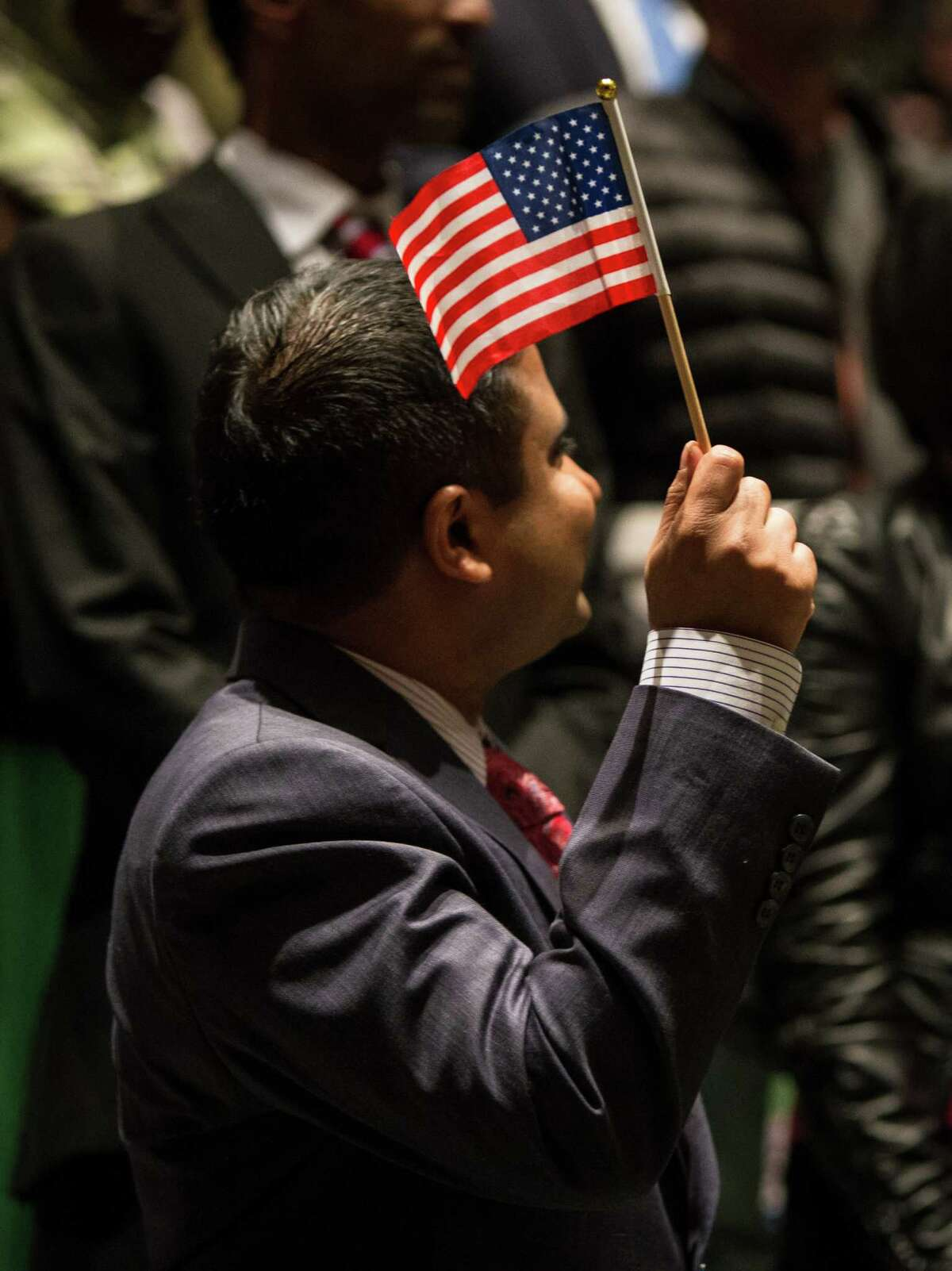 A candidate waves an American flag at the National Library Week annual naturalization ceremony in the Seattle Public Library on Monday, April 13, 2014. Seattle District Director Anne Arries Corsano welcomed 75 new citizens with the Oath of Allegiance.