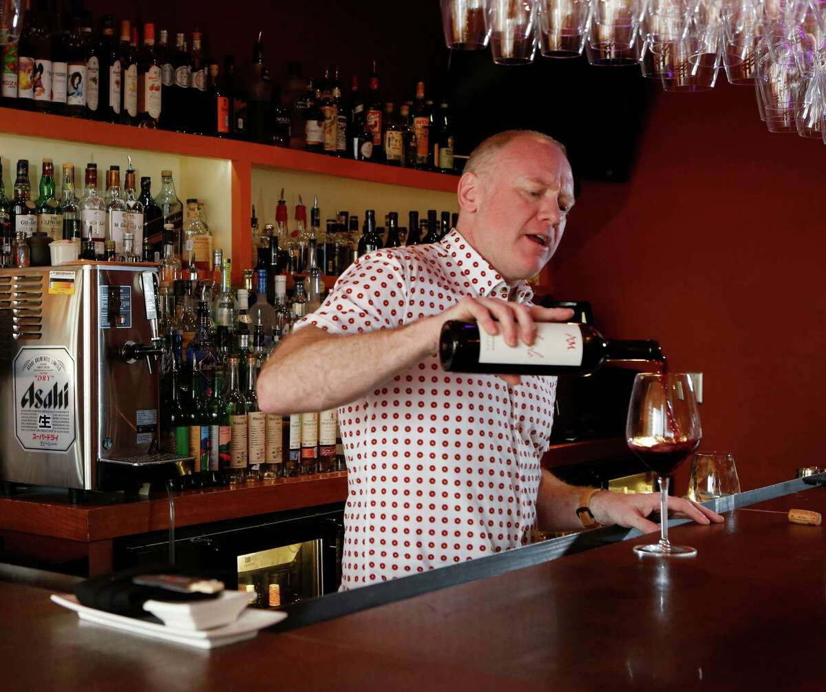 Dale Ellington pours a glass of Agri Maremma Ciliegiolo 2013, from Tuscany, at Kata Robata Wednesday, April 1, 2015, in Houston. ( Jon Shapley / Houston Chronicle )
