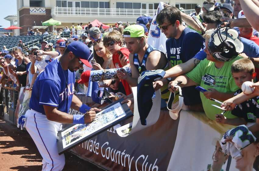 Seattle Seahawks quarterback Russell Wilson signs autographs before a spring training baseball game between the Texas Rangers and the San Diego Padres Saturday, March 28, 2015, in Surprise, Ariz. (AP Photo/Lenny Ignelzi)