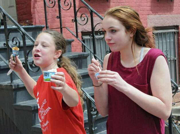 """Sophia Bon, 12, left, and Megan Close, 12, both of Albany enjoy ice cream at the end of the line outside Ben & Jerry's Ice Cream Shop on Lark St. during """"Free Cone Day"""" on Tuesday, April 14, 2015 in Albany, N.Y. The girls are in line for the a second time. Every year the ice cream shop gives away free cones from 12-8pm on this day. (Lori Van Buren / Times Union) Photo: Lori Van Buren / 00031428A"""
