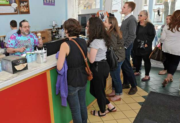 """Co-owner Michael Sperduto, left, serves ice cream cones to customers at Ben & Jerry's Ice Cream Shop on Lark St. during """"Free Cone Day"""" on Tuesday, April 14, 2015 in Albany, N.Y. Every year the ice cream shop gives away free cones from 12-8pm on this day. (Lori Van Buren / Times Union) Photo: Lori Van Buren / 00031428A"""