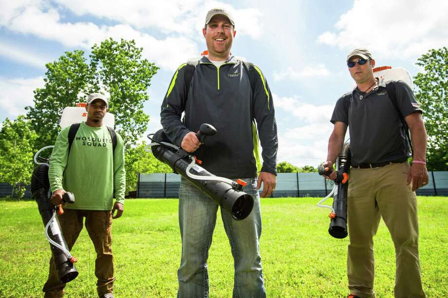 Tim Carter, a Mosquito Squad franchise owner, center, works with Mike Fisher and Mark Wright. The company's treatment lasts about 21 days.   Photo: Brett Coomer, Staff / © 2015 Houston Chronicle