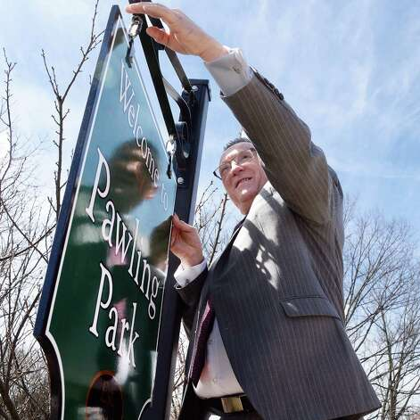 Co-committee chairman Gary Pavlic hangs a sign during the dedication of Troy's newest park, the Col. Albert Pawling Memorial Park or OPawling ParkO Tuesday April 14, 2015 in Troy, NY.  (John Carl D'Annibale / Times Union) Photo: John Carl D'Annibale / 00031424A