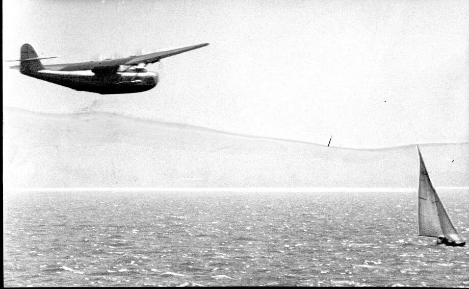 The takeoff of the Pan Am China Clipper ship from Alameda was delayed 24 minutes when this yacht sailed directly into its path as the giant plane was gaining altitude. / ONLINE_YES
