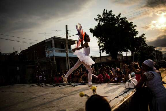 In this March 21, 2015 photo, a ballerina performs at a youth fair in her neighborhood in Santiago, Cuba. The contrast between hope and desperation is starker in eastern Cuba, poorer and isolated from the capital where detente with the United States has unleashed giddy waves of optimism. (AP Photo/Ramon Espinosa)