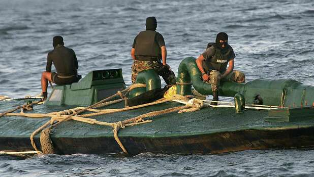 "Members of the Mexican Navy guard a submarine seized to drug traffikers in Salina Cruz port, Oaxaca state on 18 July 2008. A 10-meter-long submarine has been seized by the Mexican navy as it plied the Pacific Ocean carrying cocaine, showing the growing sophistication of drug smugglers. ""It's not a military submarine, it's 10 meters (33 feet) long and from what we know they're made in the Colombian jungle to carry drugs,"" said navy spokesman Captain Benjamin Mar after the vessel was intercepted 15 kilometers (10 miles) off the coast of Oaxaca state. According the Navy ""257 packages were assessed, with a weight brought near of 22.5 kg each one, which gives a total weight of 5,815 kg approximately.    AFP PHOTO / Juan Carlos Reyes Photo: JUAN CARLOS REYES, Getty Images / 2008 AFP"