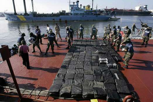 "Members of the Mexican Navy unload packages of cocain from a motorboat, seized in a submarine in Salina Cruz port, Oaxaca state on 18 July 2008. A 10-meter-long submarine has been seized by the Mexican navy as it plied the Pacific Ocean carrying cocaine, showing the growing sophistication of drug smugglers. ""It's not a military submarine, it's 10 meters (33 feet) long and from what we know they're made in the Colombian jungle to carry drugs,"" said navy spokesman Captain Benjamin Mar after the vessel was intercepted 15 kilometers (10 miles) off the coast of Oaxaca state. According the Navy ""257 packages were assessed, with a weight brought near of 22.5 kg each one, which gives a total weight of 5,815 kg approximately.    AFP PHOTO / Juan Carlos Reyes Photo: JUAN CARLOS REYES, Getty Images / 2008 AFP"