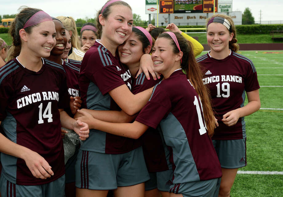 Cinco Ranch senior midfielder Julia  Echavarry, center, gets a hug from senior Madee Gallagher and sophomore Shaylee Anaya with senior midfielder Kristen Hutar and sophomore defender Jessica Moore looking on after the Cougars' 4-0 win over Seven Lakes in their Region III Class regional final. Photo: Jerry Baker, Freelance