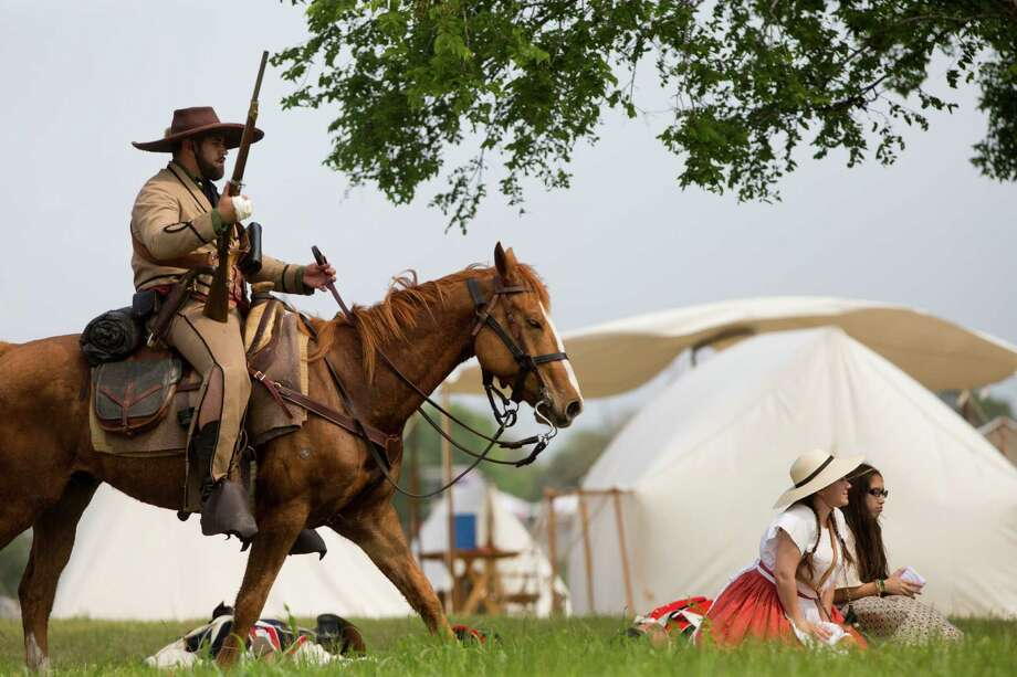 A re-enactor of the Texian army rides through the camp of the Mexican army after the Texians beat the Mexicans in a re-enactment of the Battle of Jacinto during last year's San Jacinto Day Festival at the San Jacinto Monument in La Porte. This year's admission-free celebration will be 10 a.m.-6 p.m. April 18. Photo: Marie D. De Jesus, Staff / © 2014 Houston Chronicle