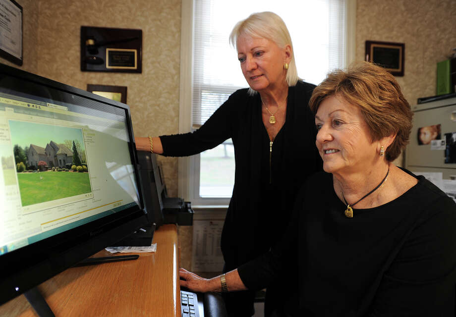 Linda Schauwecker, left, and Susan Coyle, co-owners of Real Estate Two, Inc., pull up some current listings in their office in the Huntington section of Shelton, Conn. on Tuesday, April 14, 2015. Photo: Brian A. Pounds / Connecticut Post