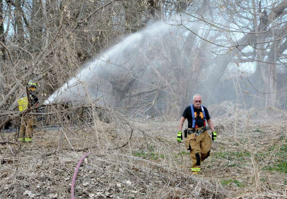 Firefighters finish extinguishing a brush fire between the bike path and the Mohawk River near Schenectady County Community College on Tuesday, April 14, 2015 in Albany, N.Y. (Lori Van Buren / Times Union)