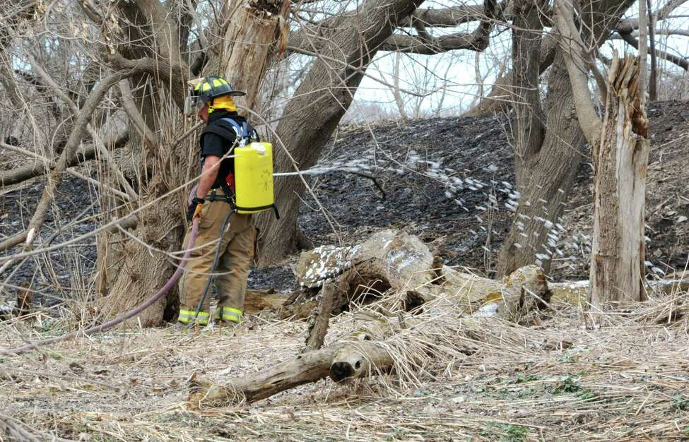 Firefighters finish extinguishing a brush fire between the bike path and the Mohawk River near Schenectady County Community College on Tuesday, April 14, 2015 in Schenectady, N.Y. (Lori Van Buren / Times Union)