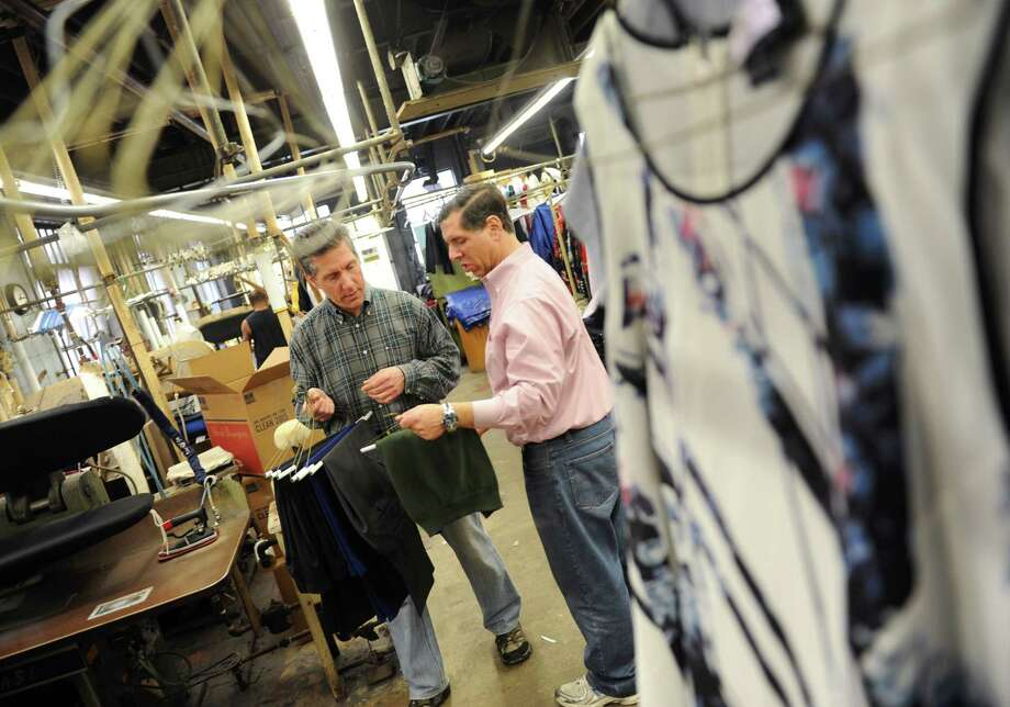 Shop co-owners and brothers Kerry Wolfe, left, and Rick Wolfe work at Wolfe's Cleaners in Stamford, Conn. Tuesday, April 7, 2015.  The family-run cleaners is celebrating its 60th anniversary this year. Photo: Tyler Sizemore / Greenwich Time