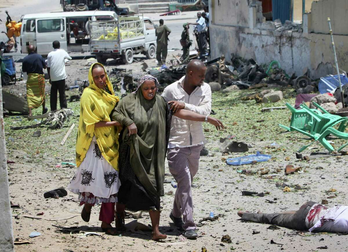 People assist a woman who was wounded when a car bomb detonated at the gates of a government office complex in the capital Mogadishu, Somalia.