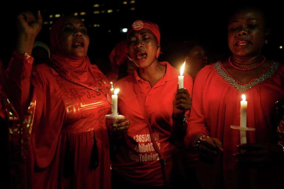 People hold candles as they sing during a vigil to mark the one year anniversary of the abduction of girls studying at the Chibok government secondary school, Abuja, Nigeria, Tuesday, April 14, 2015. On the first anniversary of the day 276 schoolgirls were snatched in the middle of the night as they prepared to write science exams at their boarding school in northeastern Nigeria, President-elect Muhammadu Buhari said he cannot promise to find the 219 who are still missing. (AP Photo/Sunday Alamba) Photo: Sunday  Alamba, STF / AP