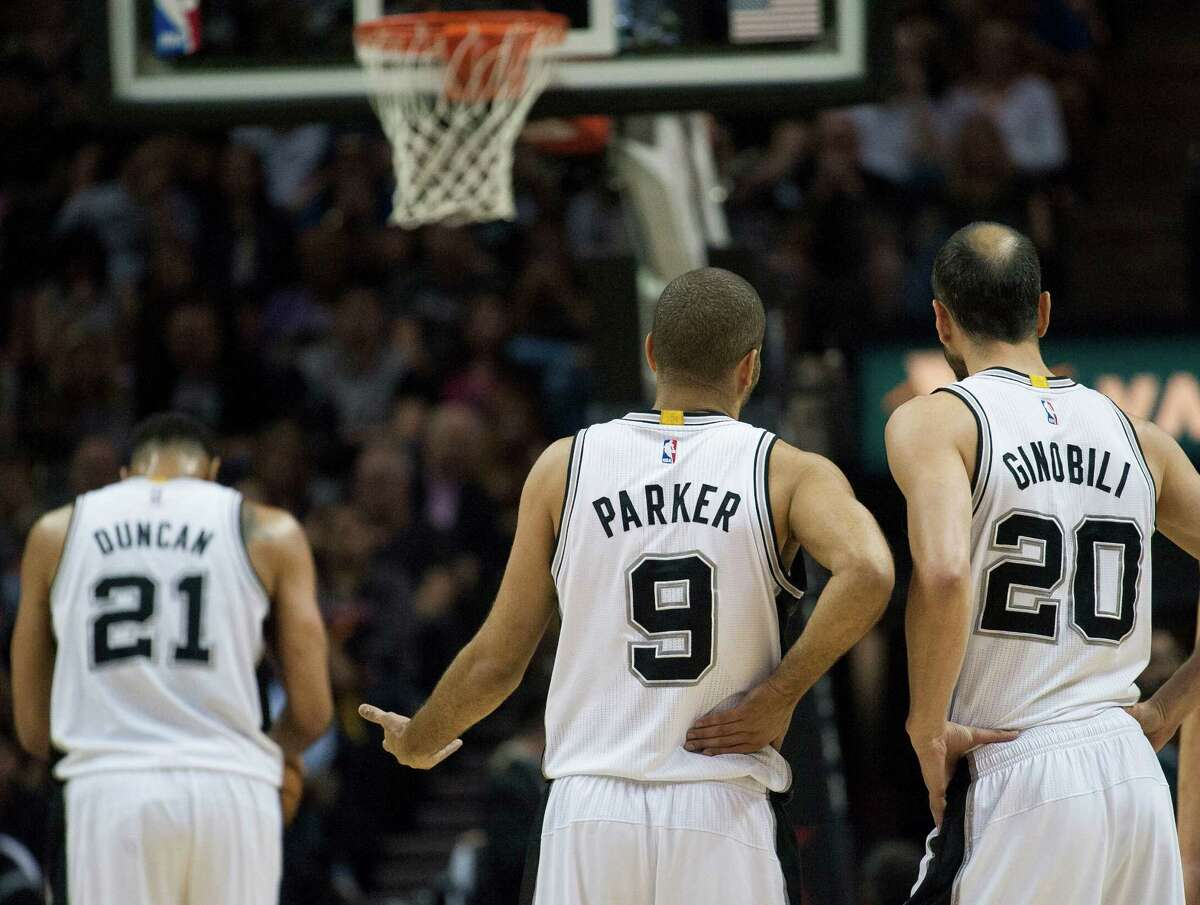 The Spurs' Tony Parker and Manu Ginobili talk on the court as Tim Duncan shoots a free throw during the first half against the Golden State Warriors, on April 5, 2015, in San Antonio. San Antonio won 107-92.