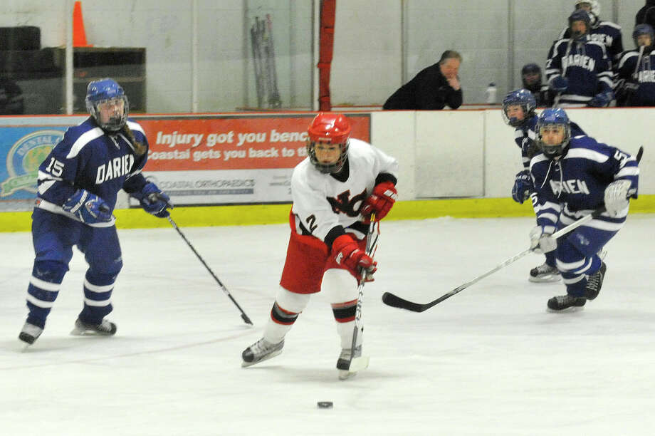 New Canaan's Catherine Granito skates past two Darien defenders. Garnito is the 2015 Heart Connecticut Media Group Super 10 MVP. Photo: Jason Rearick / Stamford Advocate