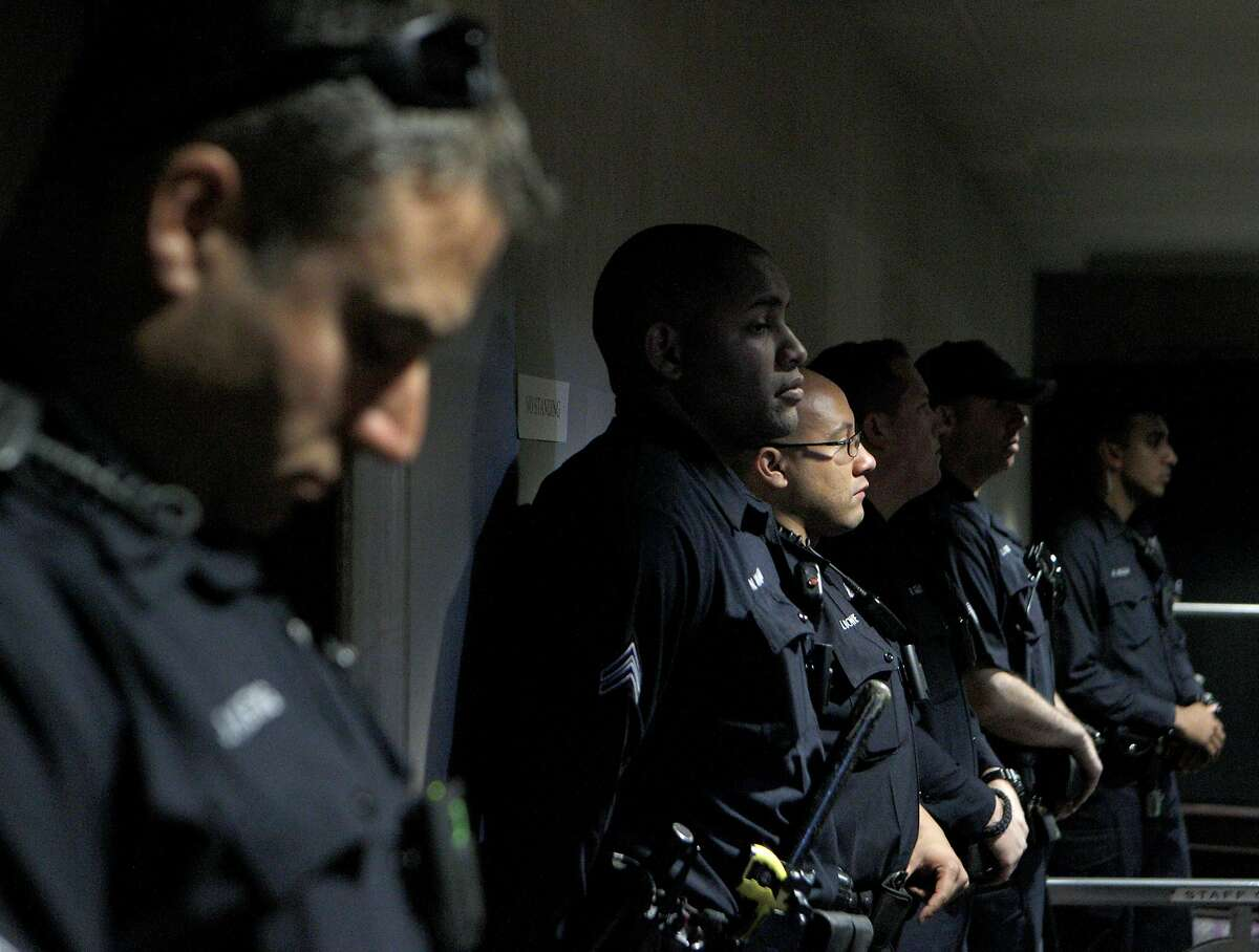 Oakland police monitor demonstrators inside City Hall during a protest against police officers, Tuesday, April 14, 2015, in Oakland, Calif.