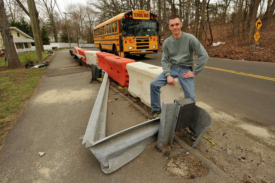 Jason Bealer sits on the replacement guard rails in front of his home on Toms Road in Stamford, Conn., on Tuesday, April 14, 2015. Residents on the top of the hill at the curve are concerned with the number of accidents there. Bealer has lived there for three years and has witnessed at least nine accidents. He is concerned about the safety of school children from Dolan Middle School that walk on the sidewalk. Photo: Jason Rearick / Stamford Advocate