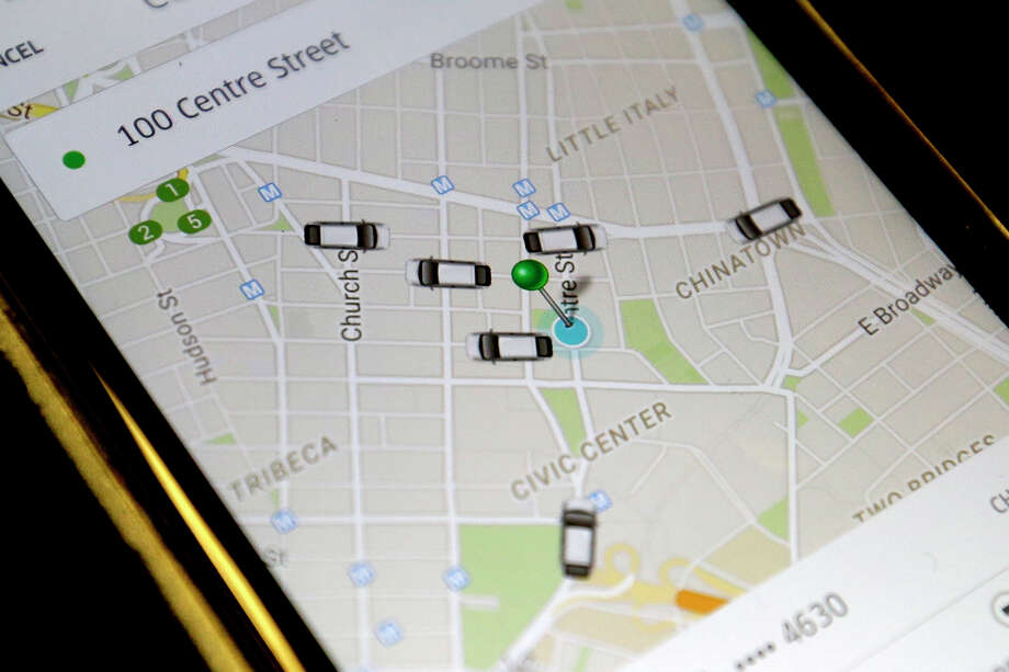 The Uber app displays cars available to make a pickup in downtown Manhattan on a smart phone, in New York. In many cities, including Houston, the prevalence of Uber drivers have made them able to arrive quicker than cabs.(AP Photo/Mary Altaffer) Photo: Mary Altaffer, STF / AP