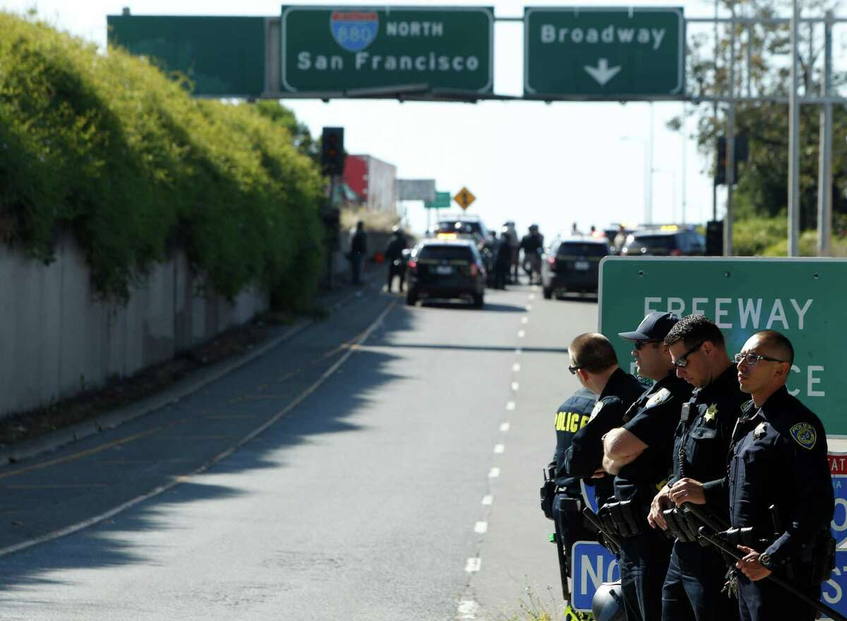 CHP, BART and Oakland police officers block the Jackson Street freeway entrance after demonstrators stormed onto the freeway for a protest against police, Tuesday, April 14, 2015, in Oakland, Calif.