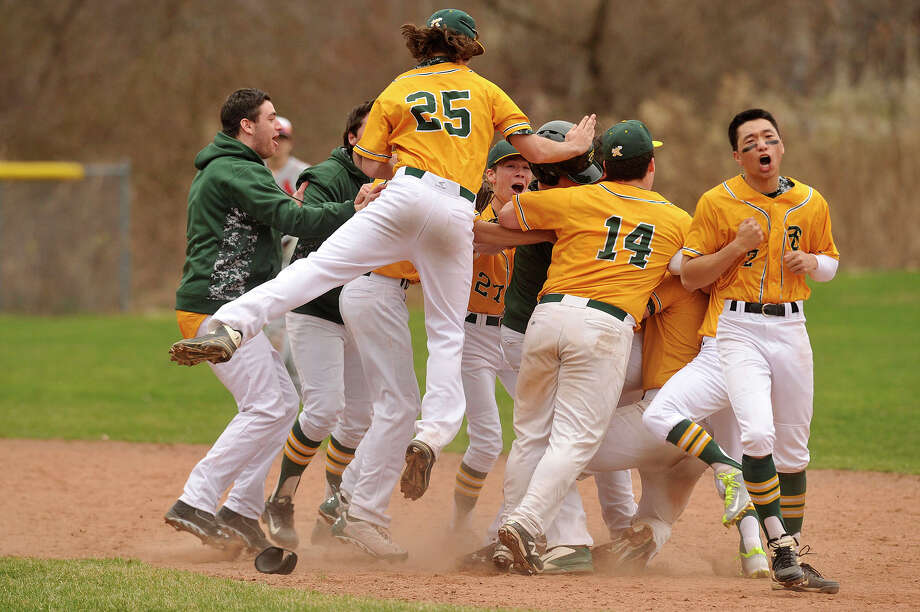 Trinity Catholic players swarm around their team mate Anthony Hoegemann after he brought in the winning run in bottom of the seventh during the Crusaders' baseball game against Greenwich at Trinity Catholic High School in Stamford, Conn., on Tuesday, April 14, 2015. Trinity came from behind in the last inning to beat Greenwich, 6-5. Photo: Jason Rearick / Stamford Advocate
