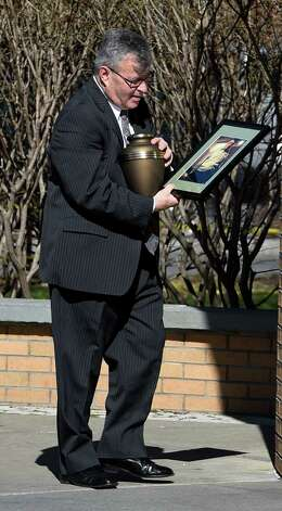 Mark Phillips, co-owner of the William J. Burke & Sons Funeral Home arrives with an urn carrying the remains  and an image of Dean Martin at the St. Clements Church Tuesday morning April 14, 2015 in Saratoga Springs, N.Y.  for Martin's funeral service.   (Skip Dickstein/Times Union) Photo: SKIP DICKSTEIN / 00031402A