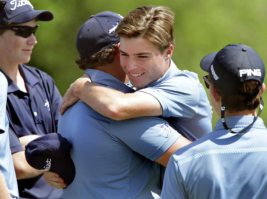 Sean Meehan, of Johnson High School, facing, is hugged by team mate Marshall Martin, left, for finishing first after the final round of the Region IV-6A boys high school golf tournament held at Cedar Creek Golf Course.  Tuesday, April 14, 2015. Photo: Bob Owen, Staff / San Antonio Express-News / ©2015 San Antonio Express-News