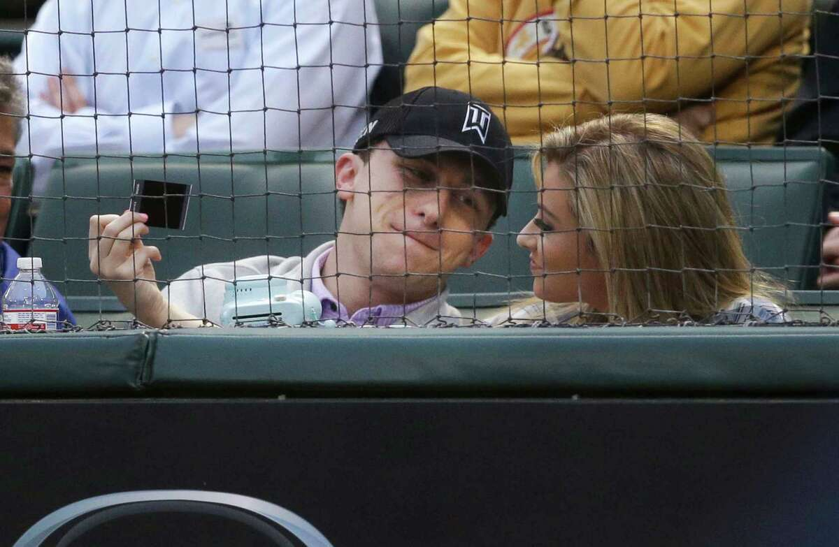 Cleveland Browns quarterback Johnny Manziel, left, sits in the stands during a baseball game between the Los Angeles Angels and Texas Rangers in Arlington, Texas, Tuesday, April 14, 2015. (AP Photo/LM Otero)