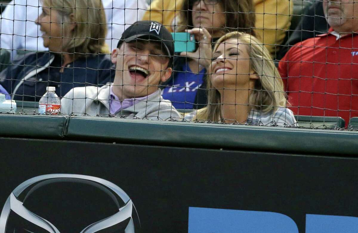 Cleveland Browns quarterback Johnny Manziel, left, laughs while sitting in the stands during a baseball game between the Los Angeles Angels and Texas Rangers in Arlington, Texas, Tuesday, April 14, 2015. (AP Photo/LM Otero)