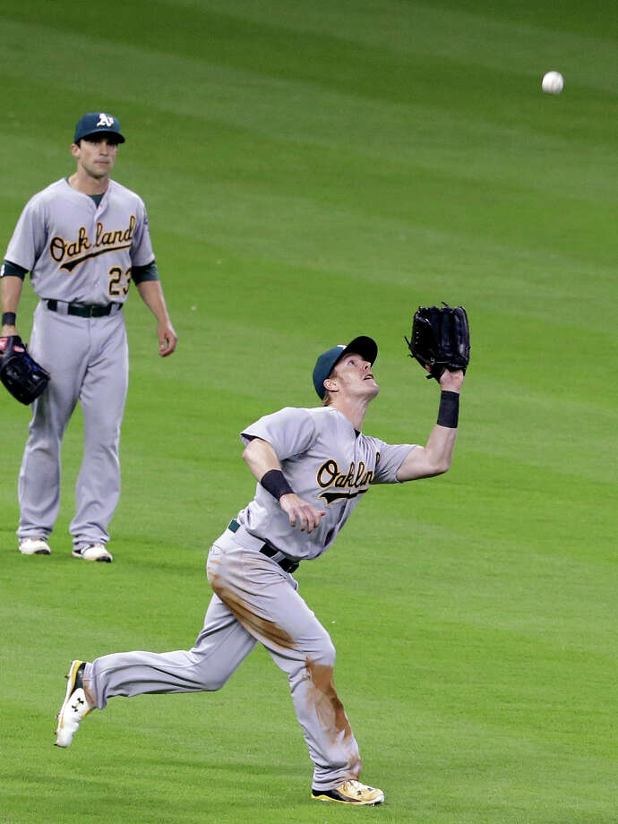 Oakland Athletics left fielder Mark Canha, right, makes the catch for the out on Houston Astros' Jose Altuve as Sam Fuld (23) backs him up in the fifth inning of a baseball game Tuesday, April 14, 2015, in Houston. (AP Photo/Pat Sullivan) Photo: Pat Sullivan / Associated Press / AP