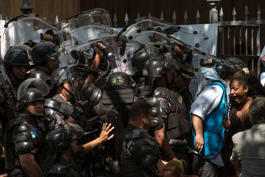 Policemen from the special unit CHOQUE enter the occupied building to push out squatters, in Flamengo, Rio de Janeiro, on April 14, 2015.  More than 100 squatters who had been evicted from the city port area last month invaded a week ago the building once owned by Brazilian businessman Eike Batista. Photo: Christophe Simon, AFP / Getty Images
