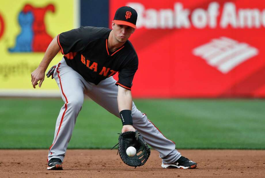 Buster Posey, fielding ground balls at first base during infield practice prior to an April game in San Diego, has learned to handle defensive duties on the infield pretty well. Photo: Lenny Ignelzi / Associated Press / AP