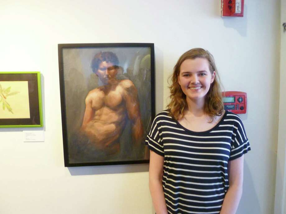 "Grayson Kennedy, 18, of New Canaan, stands alongside her painting ""Man Curly Hair,"" which took first prize in the the youth category at the Silvermine Art Center's 25th Annual Student's Exhibition. Works by art students of all ages will be on exhibit at Silvermine through May 20. Photo: Martin Cassidy / New Canaan News"
