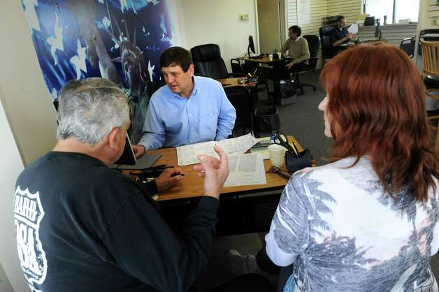 CPA and owner Ed Welch works on an income tax return with Sam and Sue Tubolino of Clifton Park at Liberty Tax Service on Tuesday, April 14, 2015, in Albany, N.Y. (Michael P. Farrell/Times Union) Photo: Michael P. Farrell / 00031434A
